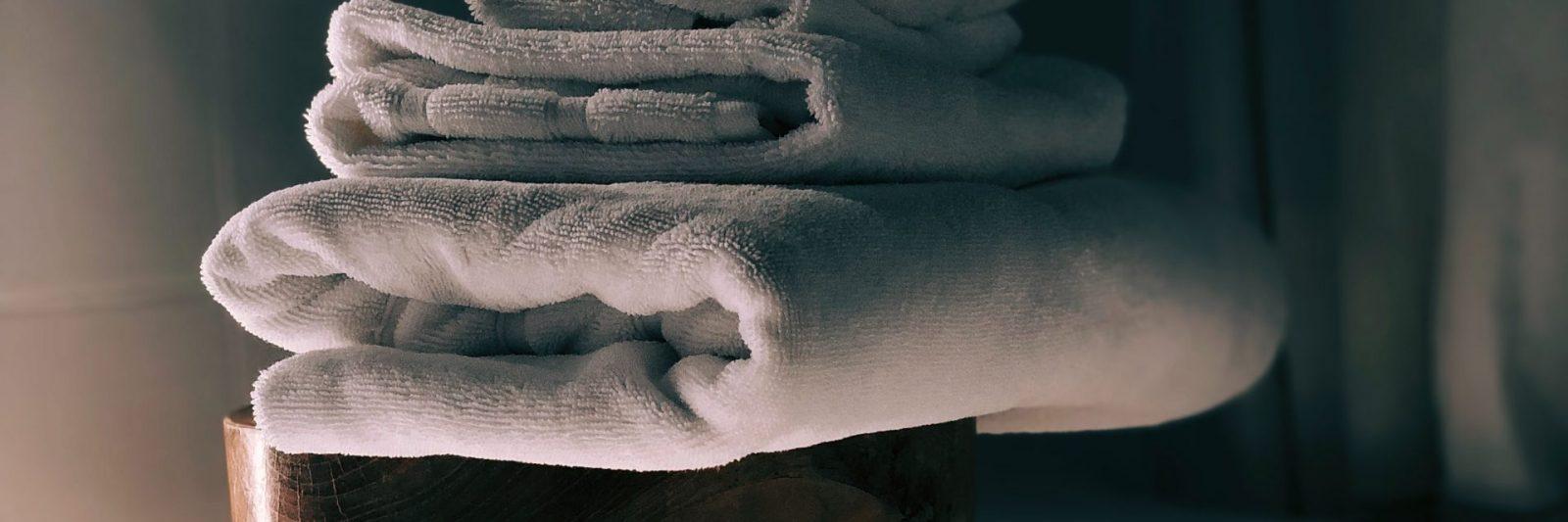 Clean towels on a stool near bathtub