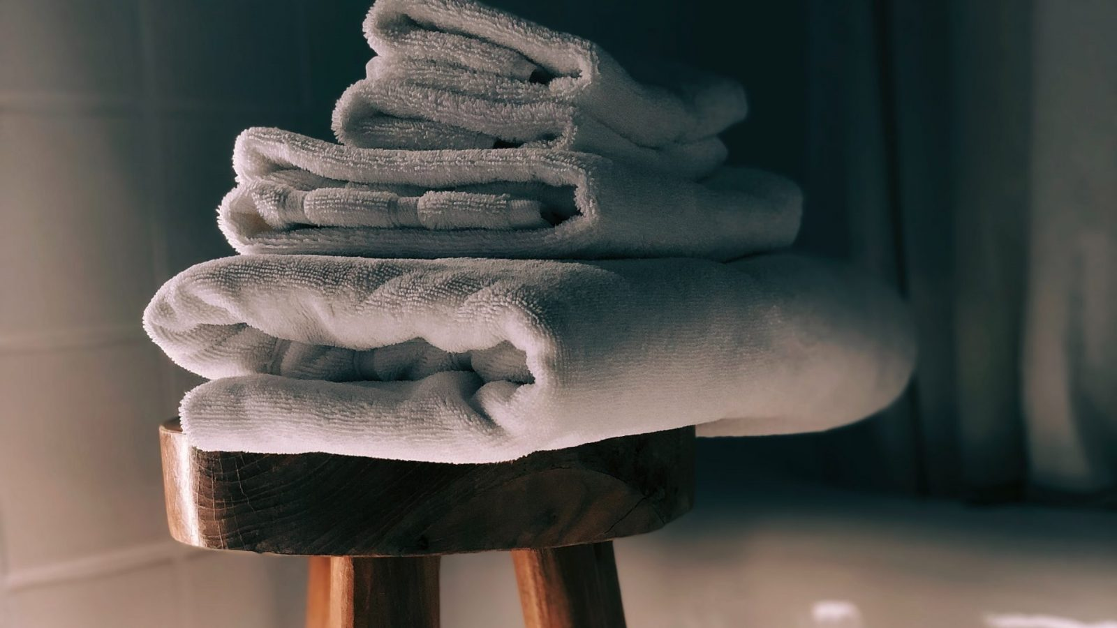 Clean towels on a stool near bathtub
